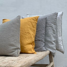 A mustard yellow natural washed linen cushion adds a pop of colour to neutral tones
