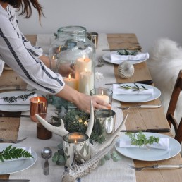 Christmas table decorations including vintage glass vessels containing candles, linen table runner and winter foliage