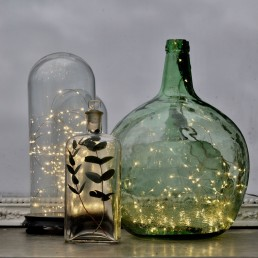 Vintage glass demijohn and other vessels containing warm yellow firefly lights - Christmas home styling ideas from Home Barn