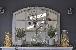 Mantelpiece with large rustic mirror, paper and glass Christmas decorations, twinkling fairylights and foliage from Home Barn